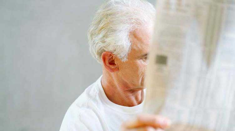 Man looking at stock prices in the paper