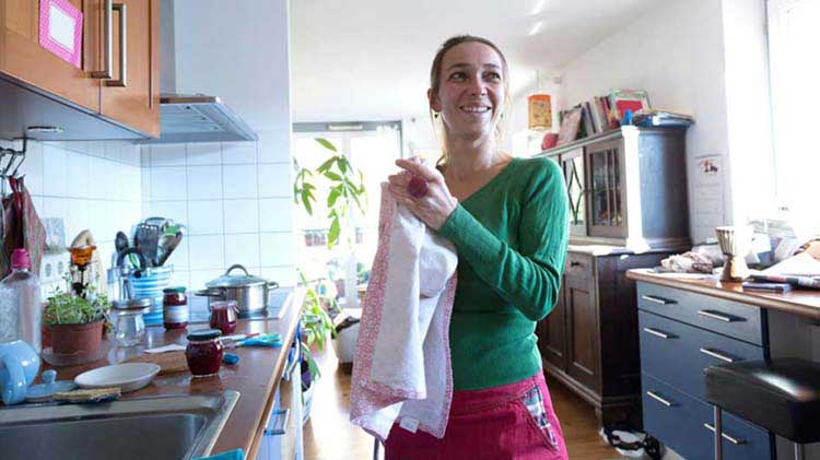 Woman in her kitchen considers capital gains on her home sale.