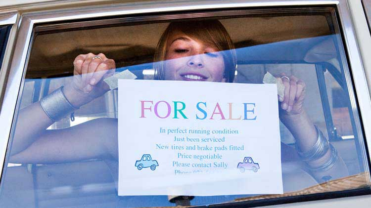 Woman hanging homemade for sale sign in car window