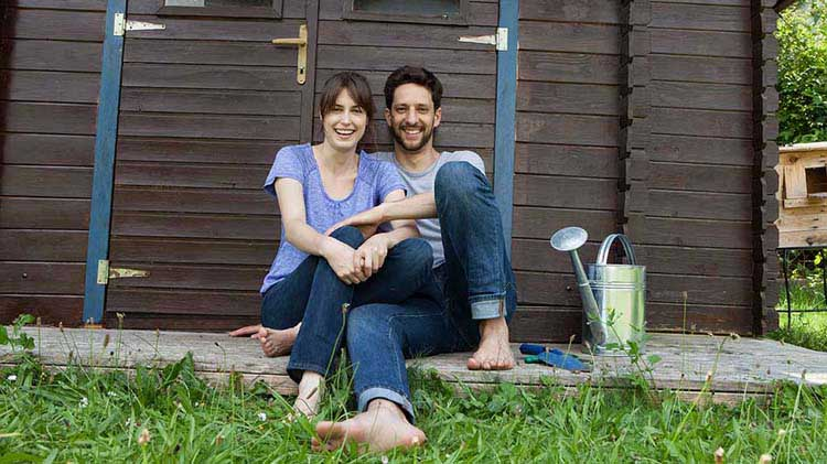 Young barefoot couple in backyard