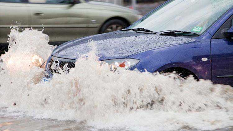 Car driving through a flooded street and possibly having flood damage as a result.