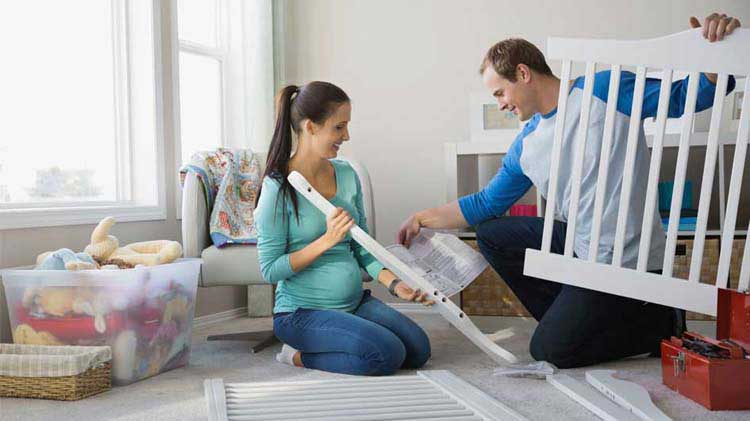 Couple practices crib safety while assembling baby's first crib.