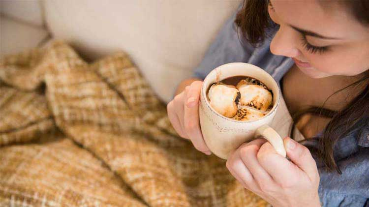 A woman enjoys her hot chocolate while wearing an electric blanket.