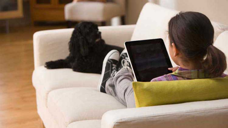 Child alone on couch looking at a tablet.