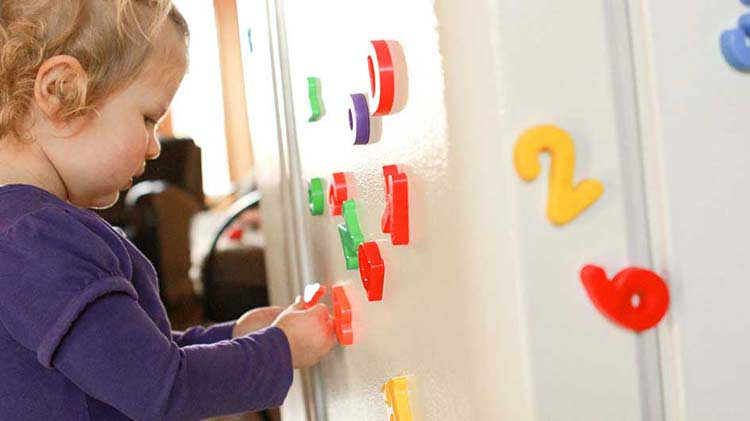 Toddler playing with refrigerator magnets