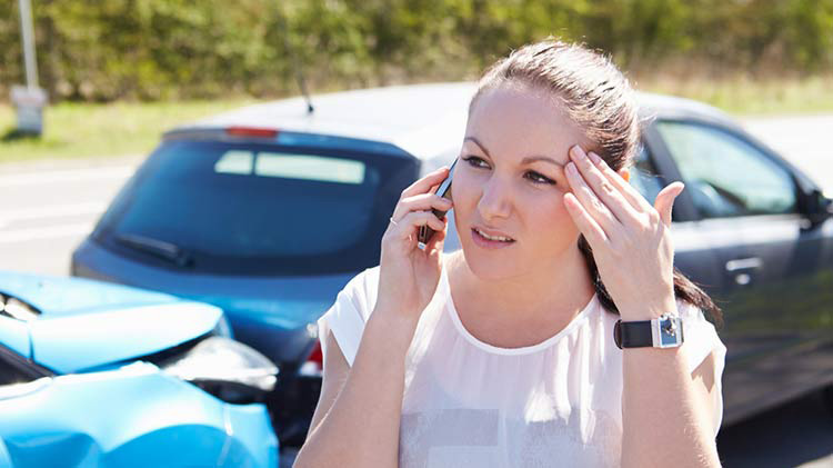 Teen on cell phone with two-car accident in background