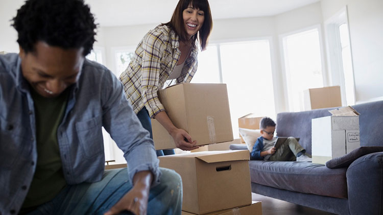 After filing a renters claim, a young couple happily unpacks moving boxes while their son reads on the couch in the background.