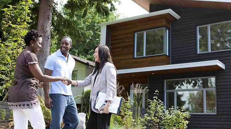 A man and a woman in front of their new house shaking hands with their realtor.