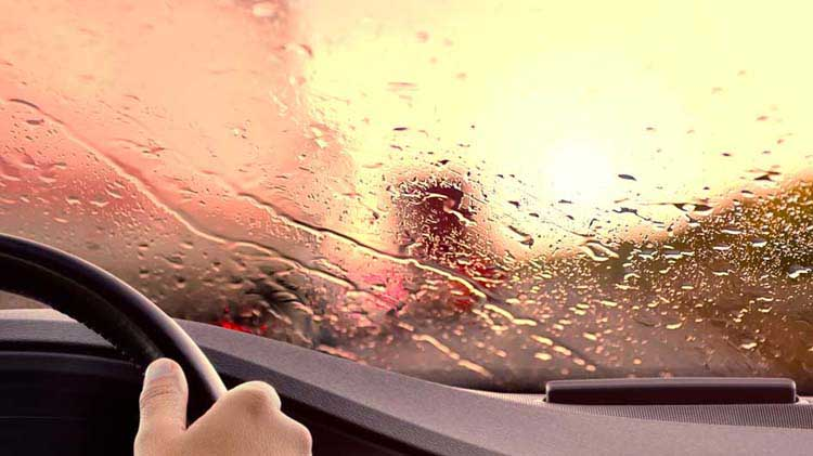 Blurred road scene shown through rain-covered windshield