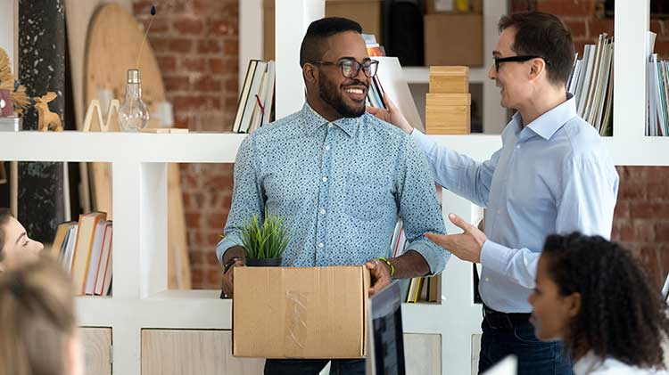 While standing in an office, a man is talking with another man about his 401(k) while carrying a box.