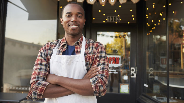 An African American man stands in front of his small business.