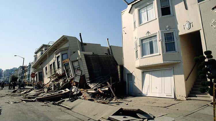 Houses with earthquake damage where one is leaning to the left and sunk in.