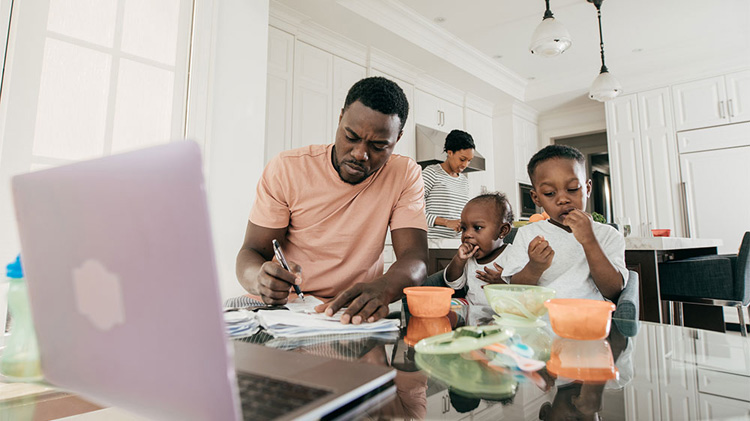 Family in kitchen, father filling out paperwork for life insurance on spouse