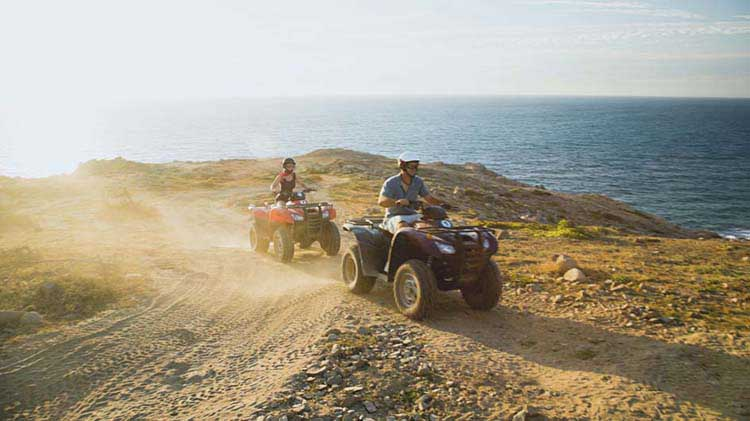 Man and woman riding ATVs on a dirt trail by the ocean