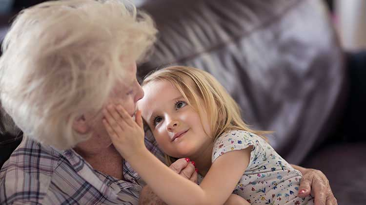 Grandparent holder her grandchild while considering life insurance