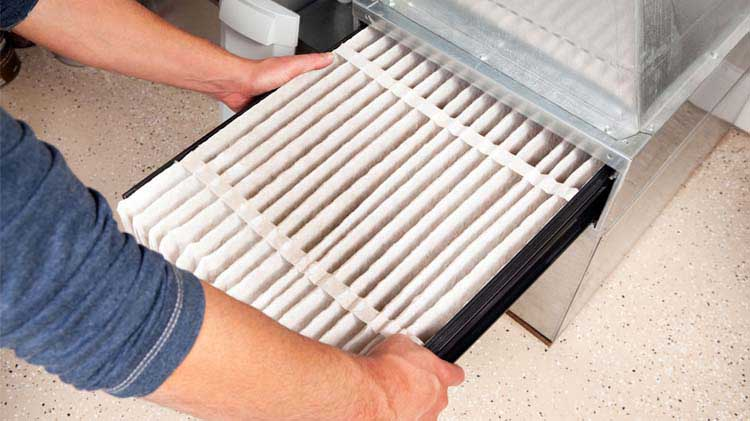 Man performing furnace maintenance by changing the furnace filter.