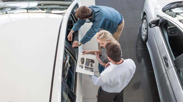 Couple looking at a new car at a car dealership
