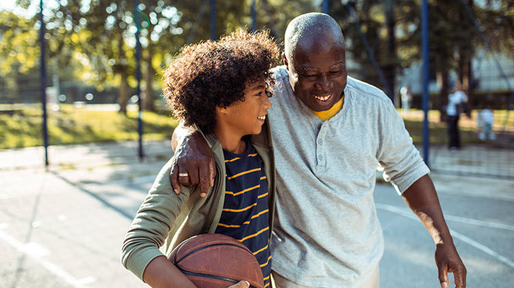 Boy carries a basketball and walks arm-in-arm with his grandfather across a basketball court.