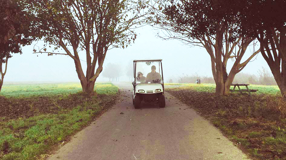 Man and child on a foggy golf course driving a golf cart