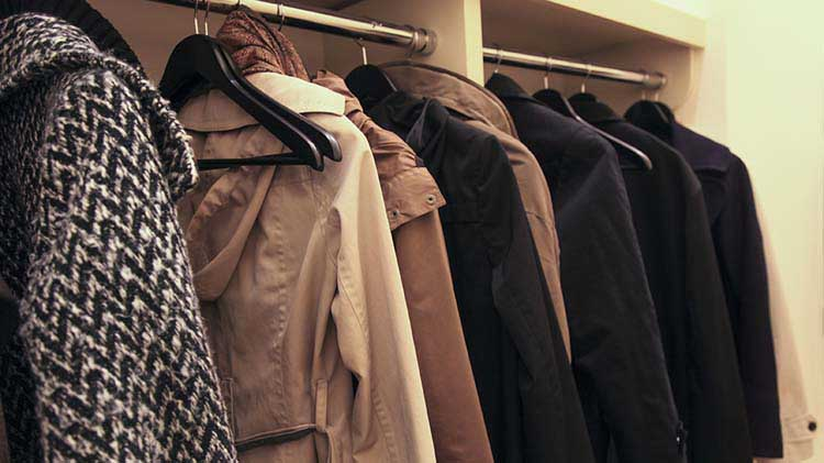 Coats are seen hanging in a closet while guests attend a house party