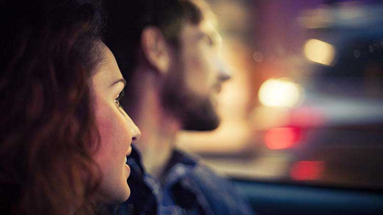 A couple is seen close up while driving a car after leaving a house party