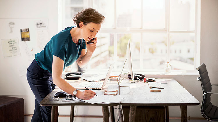 Woman working at a desk and talking on the phone.