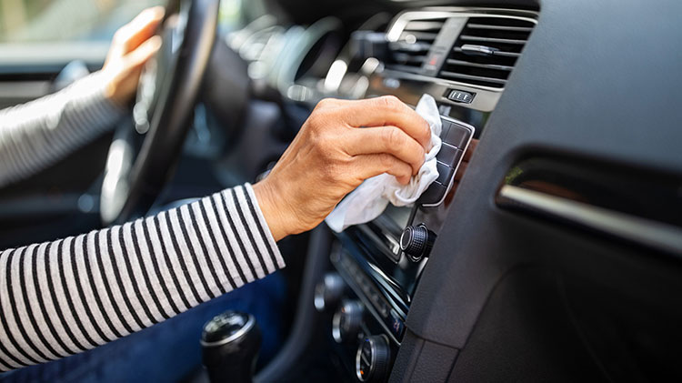 A woman wipes the vent on the dash of her car with a rag