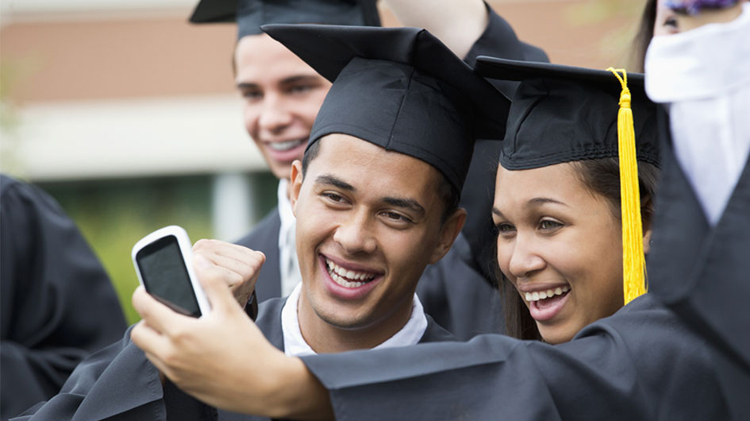 Graduates taking self-portrait together outdoors
