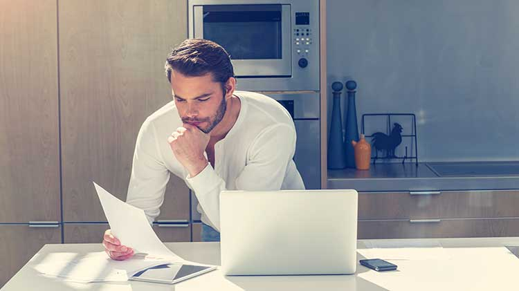 Man leaning over his kitchen counter thinking about the paper in his hand with a laptop computer nearby.