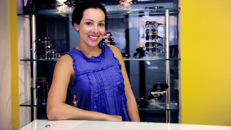 A small business owner stands at the counter in her sunglasses shop.