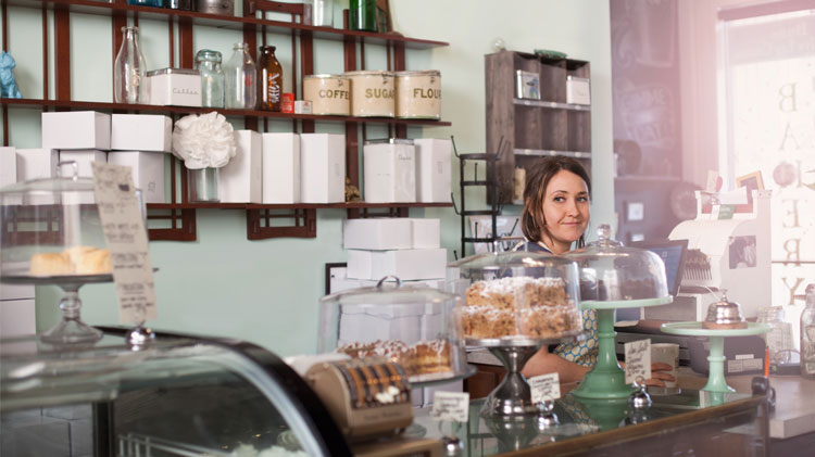 A woman small business owner stands behind the counter in her bakery.