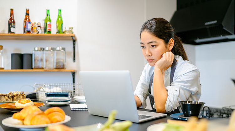 A woman sits at her computer thinking about her business.