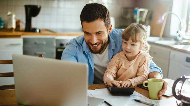 A man with his daughter sitting on his lap at the kitchen table working on a laptop managing the families savings.