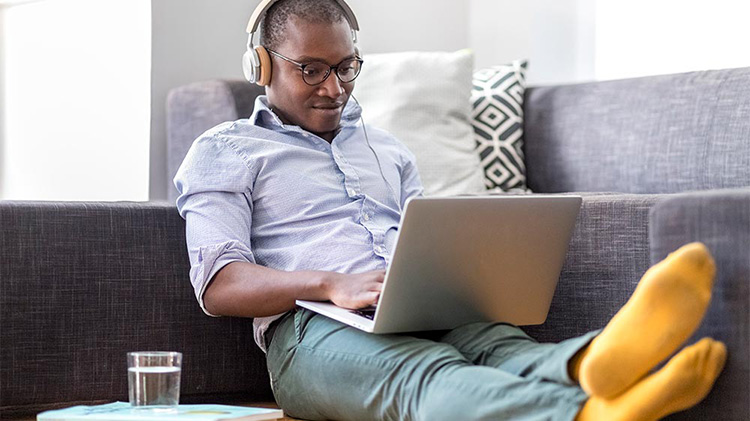 Man sitting on a couch wearing headphones while working on a computer.