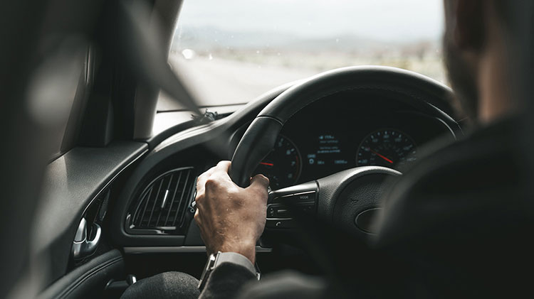 Man with hands on steering wheel