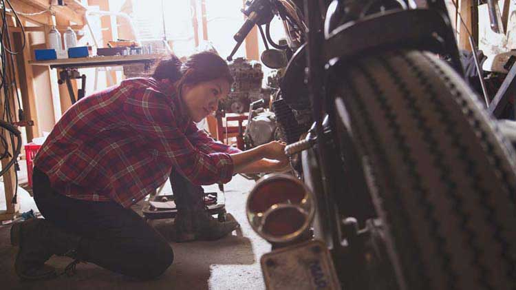 A woman mechanic working on a motorcycle