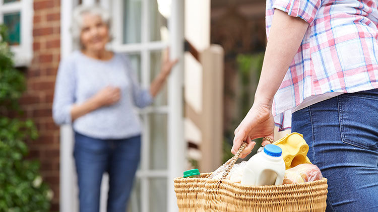 Carrying a basket of items to an elderly neighbor.