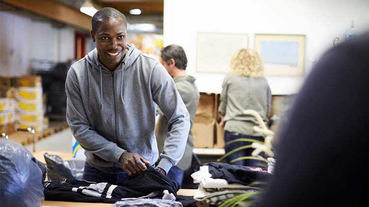 Man volunteering by packing clothes.
