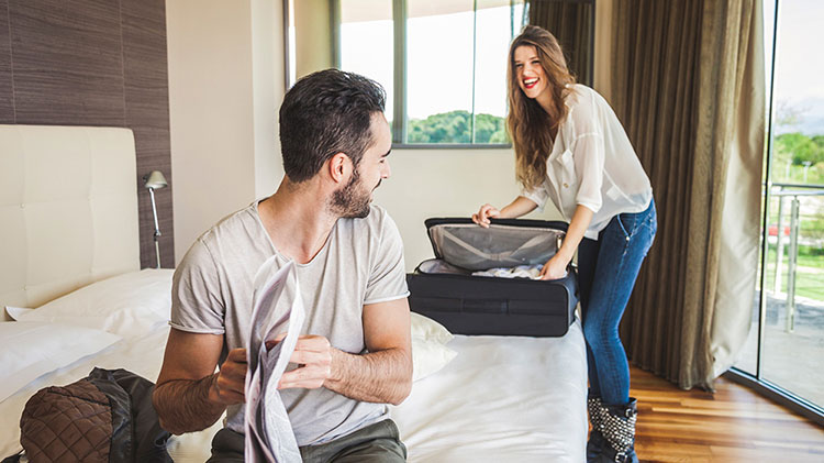 A couple unpacking for a hotel stay.