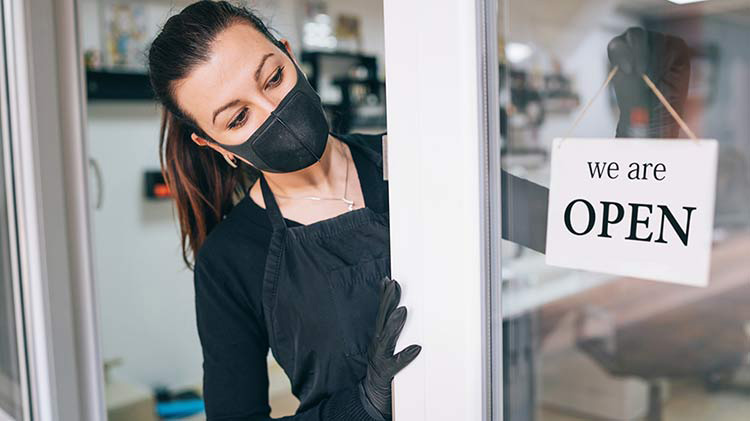 A woman wears a face mask while opening up her business