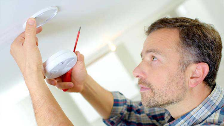 Person installing a smoke alarm