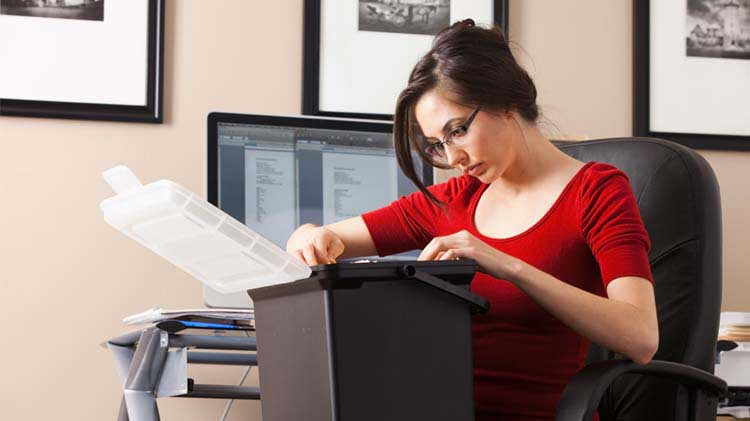 Woman reviewing file box of documents.