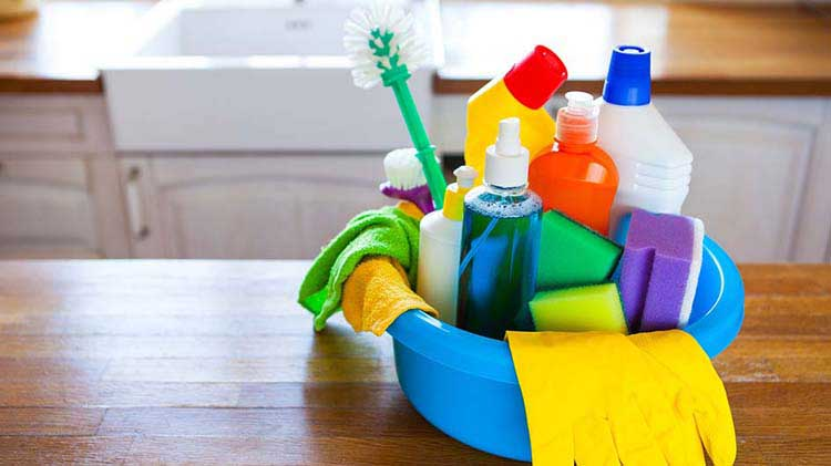 Bucket of cleaning supplies on a table