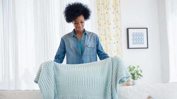 Lady folding a blanket.