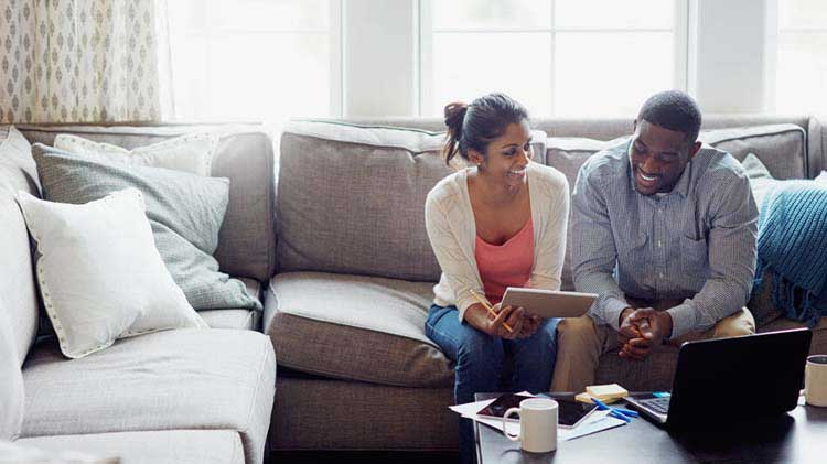 Couple sitting in living room working on taxes