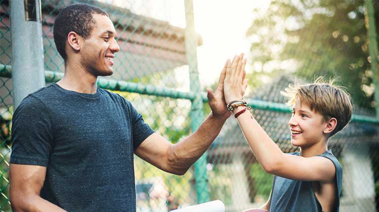 Mentor and young boy on basketball court high-fiving each other
