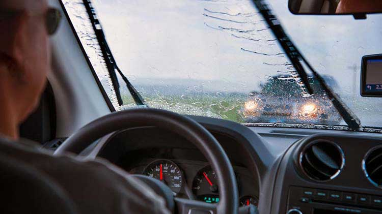 A person driving a car in the rain