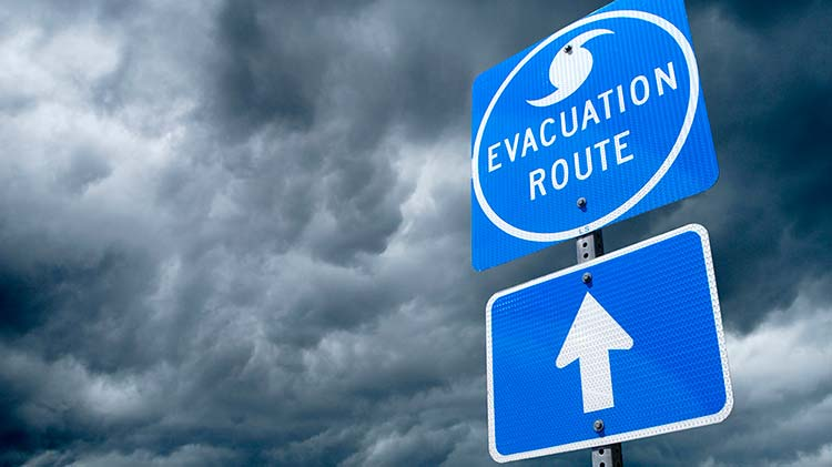 hurricane evacuation route sign with storm clouds