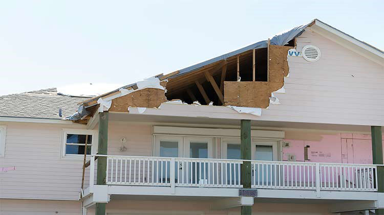 House with part of roof missing from hurricane damage.