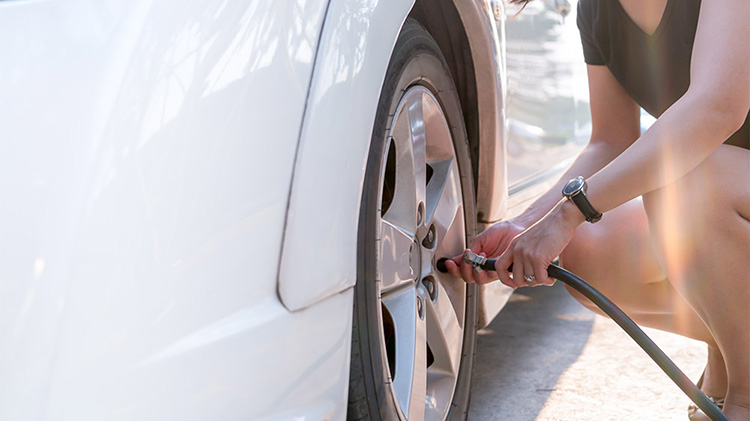 Woman maintaining tires by filling with air